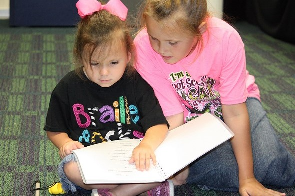 Two young girls read a Braille book together.
